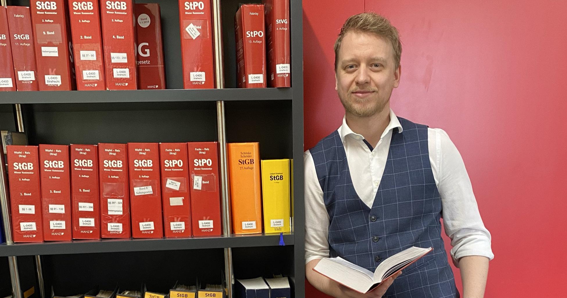 Rechtsanwalt Bernd Wiesinger lehnt an einem Bücherregal
